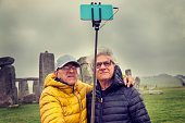 mature men friends take a selfie in the Stonehenge archaeological site - concept of active senior who travel and have fun