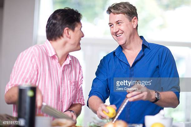 Mature men in kitchen, one grating lemon zest