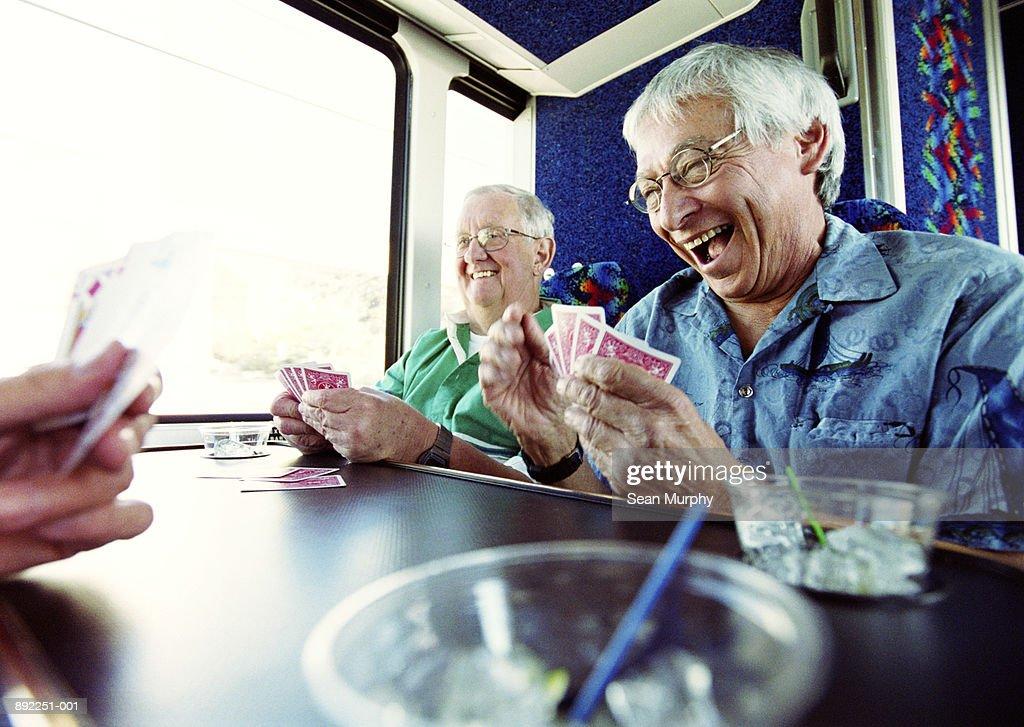 Mature men playing cards on tour bus : Stock Photo