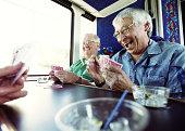 Mature men playing cards on tour bus