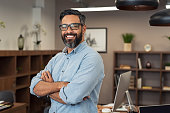 Portrait of happy mature businessman wearing spectacles and looking at camera. Multiethnic satisfied man with beard and eyeglasses feeling confident at office. Successful middle eastern business man s