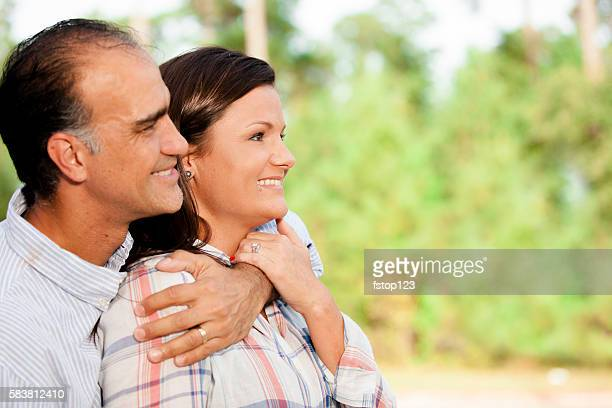 Mature, mixed-race couple outdoors in summer.