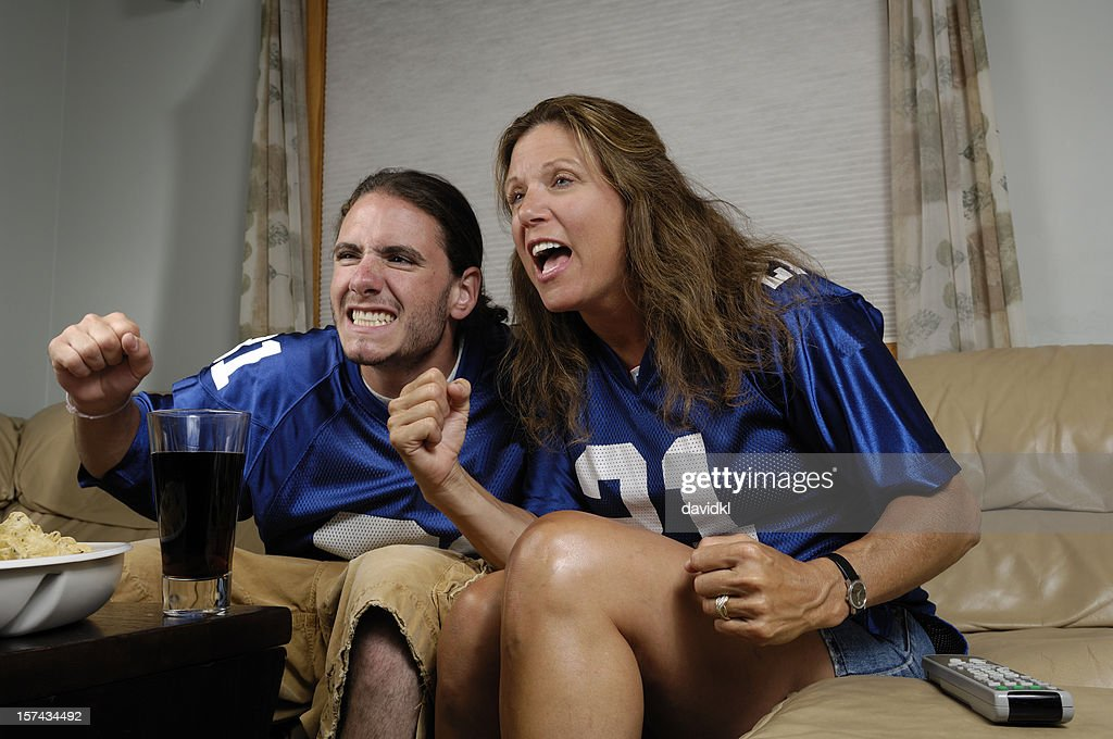 Mature mom and her teenage son watching a football game