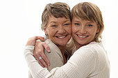 Mature mother and daughter embracing smiling, portrait