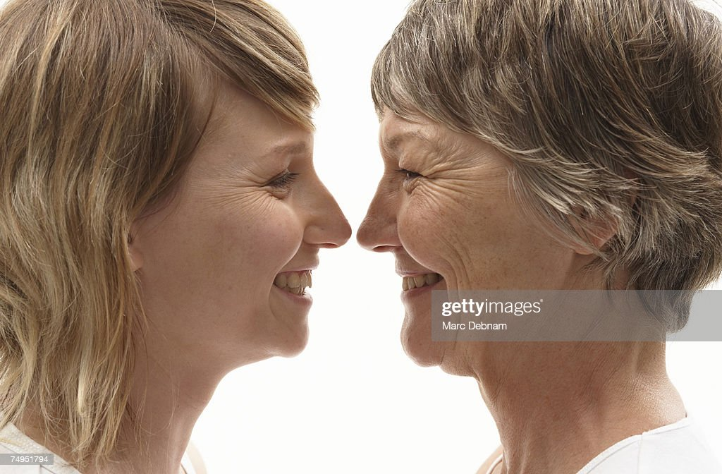 Mature mother and daughter, face to face, smiling, close-up : Stock Photo