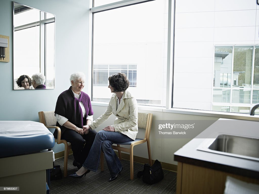 Mature mother and daughter sitting in exam room : Stock Photo