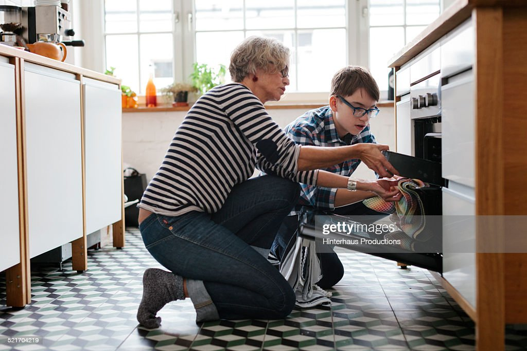 Mature Mother teaching her teenage Son how to bake : Stock Photo