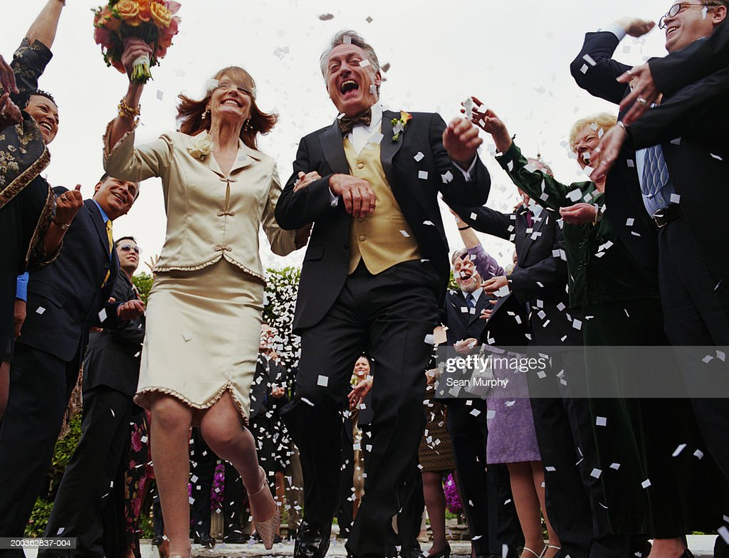 Mature newly wed couple running through confetti : Stock Photo