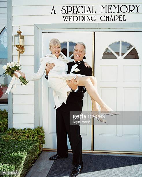 Mature Newlywed Couple Outside a Wedding Chapel in Las Vegas. Groom Carrying the Bride.