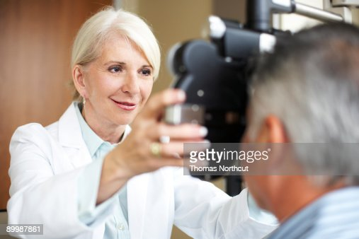 Mature Opthamologist checks a mature man's vision : Stock Photo