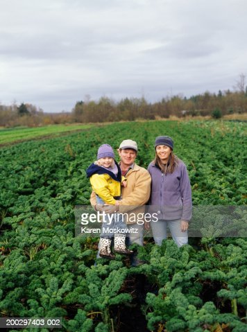 Mature parents and girl (5-7) in field on farm, smiling, portrait : Stock Photo