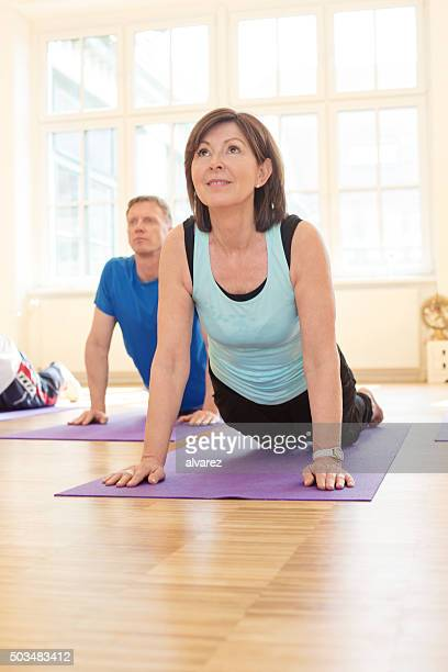 Mature people performing the cobra position in yoga class
