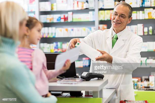Mature pharmacist packing a medicine.