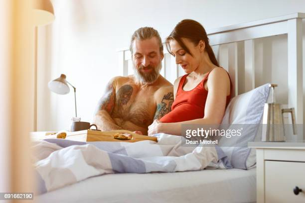 Mature pregnant couple in bedroom