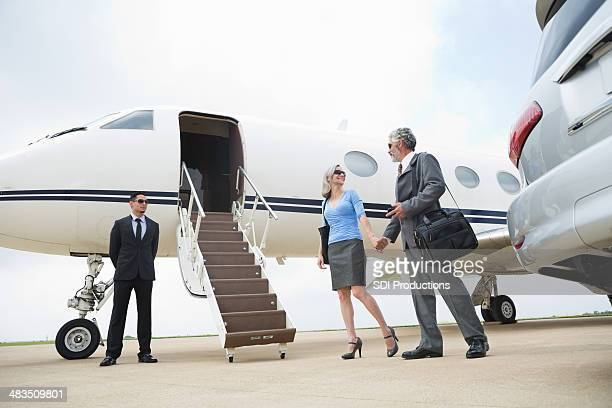 Mature professional couple travelling by luxurious private jet