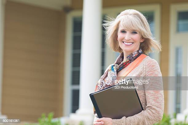 Mature professional real estate agent standing outside new home