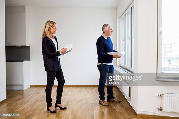 Mature real estate agents looking through window at home