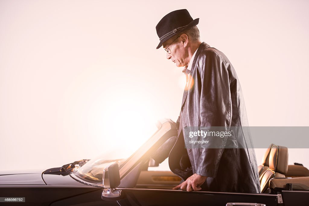 Mature retro man entering into old timer car at sunset.