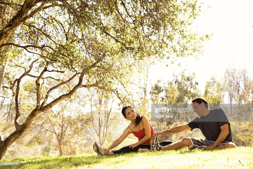 Mature running couple warming up touching toes in park