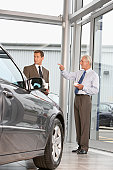Mature salesman standing with businessman in car showroom, pointing