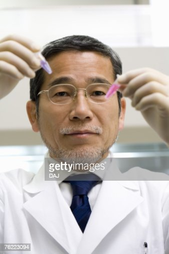 Mature scientist man looking at test tubes in laboratory, front view : Stock-Foto