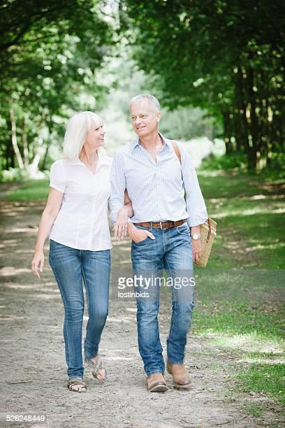 Mature/ Senior Couple Strolling Through The Park