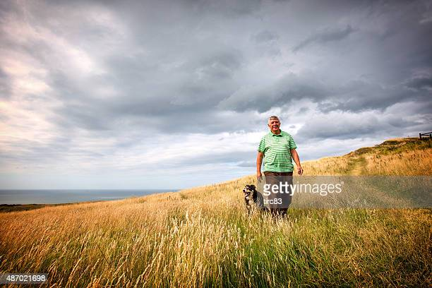 Mature senior man walking on coastal headland with sheepdog