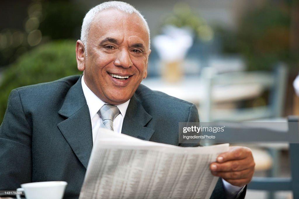 Mature smiling businessman enjoying his morning fresh newspaper in cafe. : Stock Photo