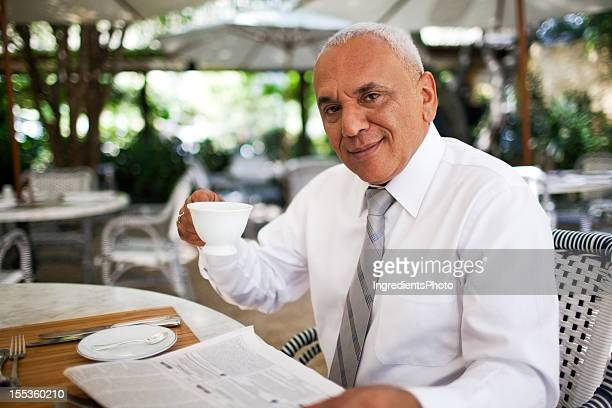 Mature smiling businessman enjoying his morning fresh newspaper in cafe.