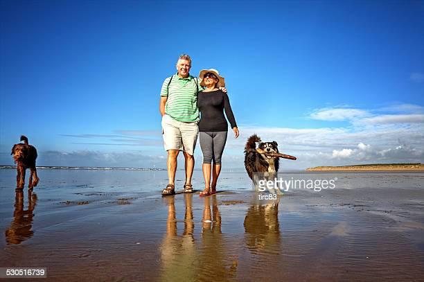 Mature smiling couple walking on the seashore