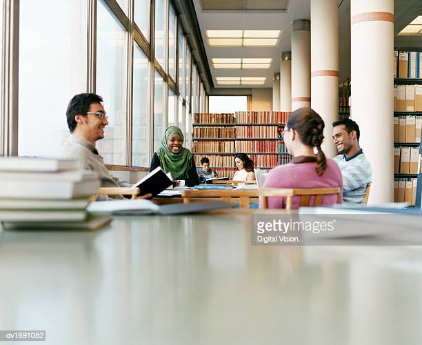 Mature Students Sitting at a Table in a University Library