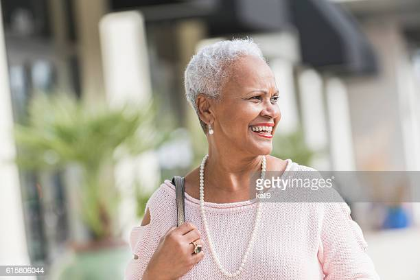 Mature, stylish African American woman walking on sidewalk