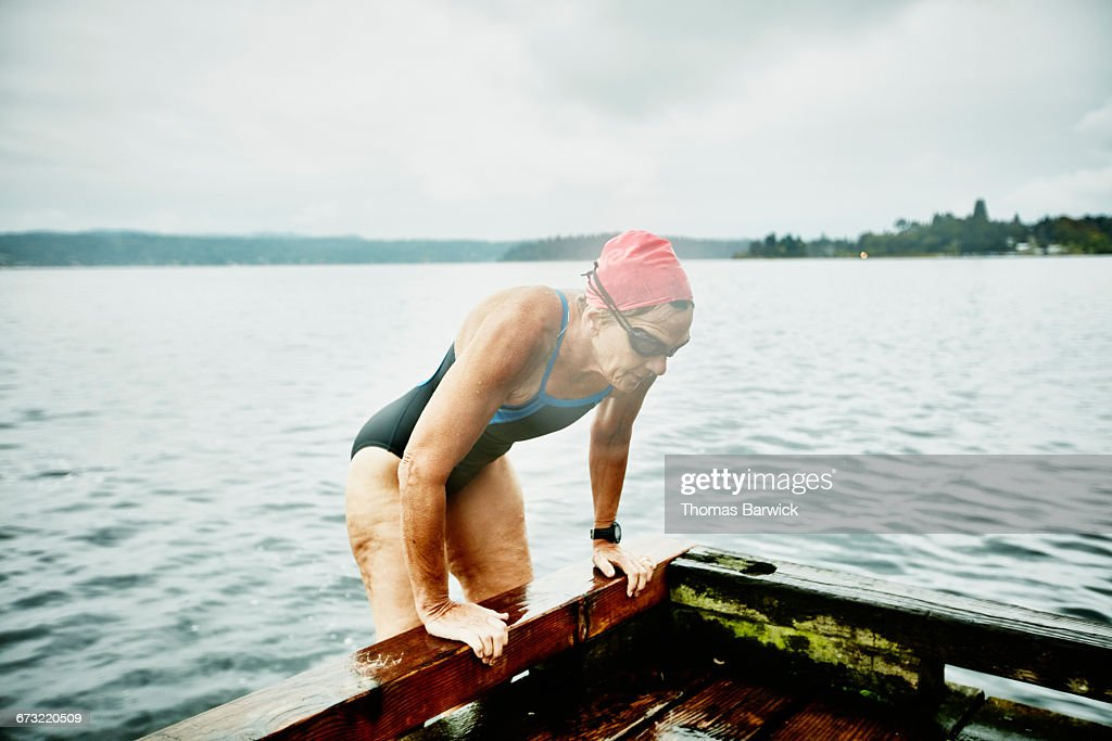 Mature swimmer climbing onto dock after swim
