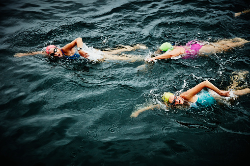 Mature swimmers on early morning open water swim