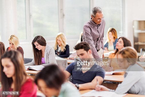 Mature teacher assisting female college student in the classroom.