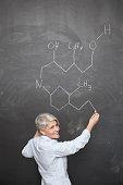 Mature teacher drawing chemical formula on blackboard