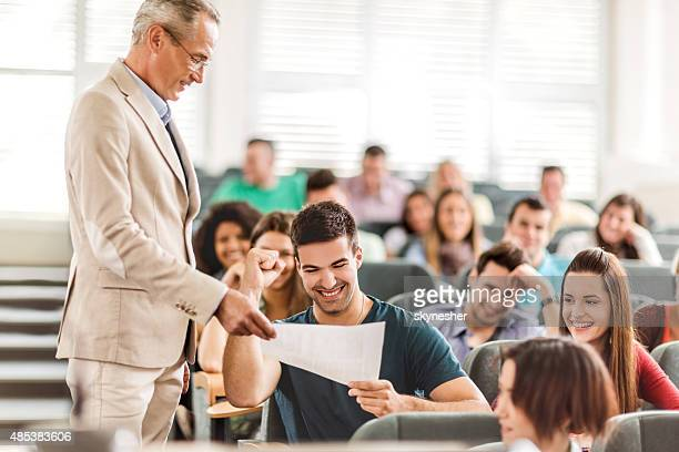 Mature teacher giving test results to cheerful student.