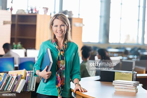 Mature teacher standing at library check-out desk