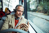 Mature tired businessman with smartphone and heaphones travellling by bus in city, listening to music.