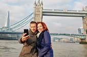 Mature tourist couple photographing selves and Tower Bridge, London, UK