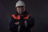 Portrait image of a mature traditional miner with his arms crossed,