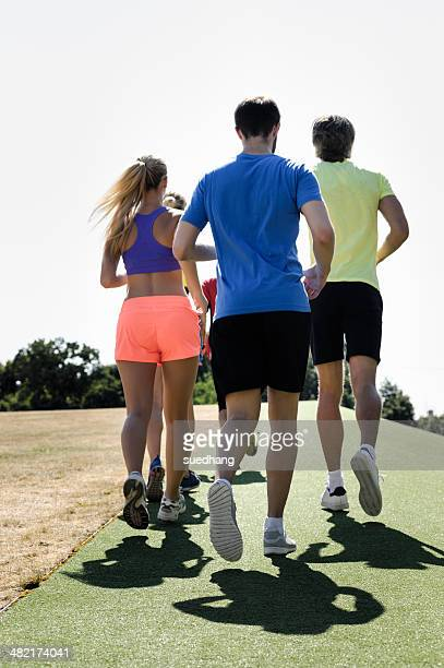 Mature trainer running with group of adults in park
