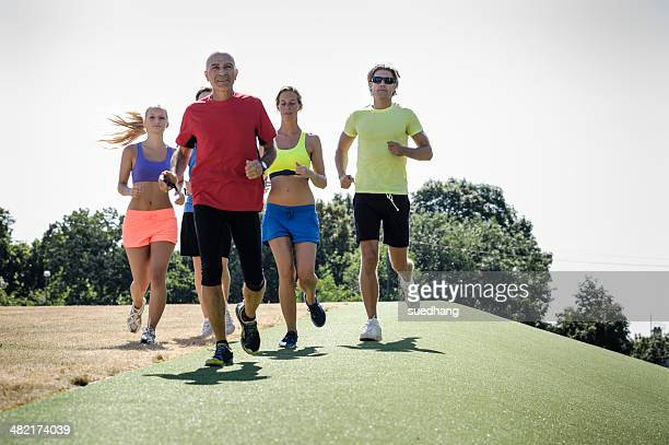 Mature trainer running with group of adults
