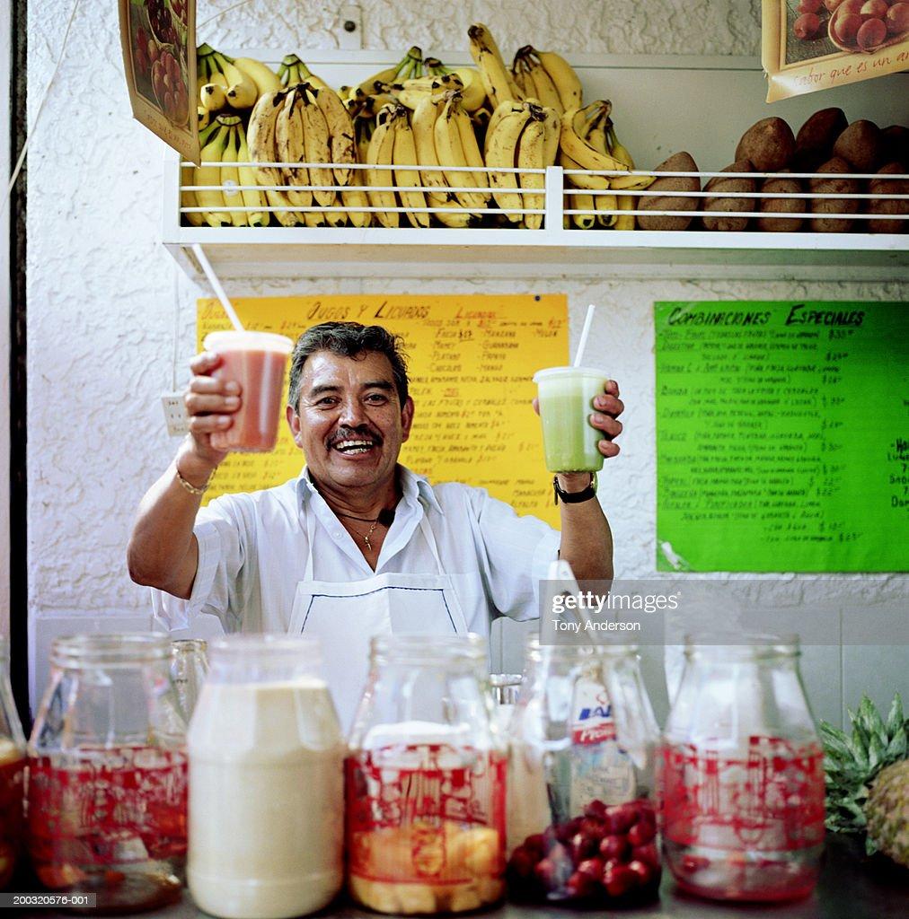 Mature vendor holding fresh juices at stand, portrait : Stock Photo