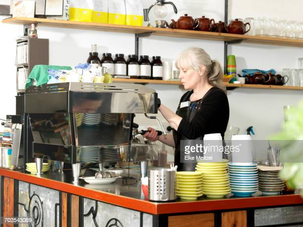 Mature waitress making coffee using coffee machine behind counter