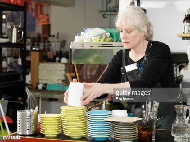Mature waitress working behind counter stacking disposable cup lids