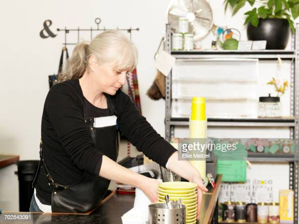 Mature waitress working behind kitchen counter stacking saucers