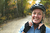 Mature woman adjusting bicycle helmet at sunset, smiling, portrait