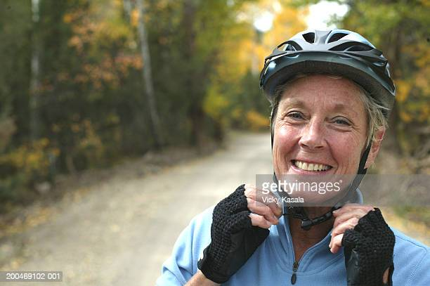 Mature woman adjusting bicycle helmet at sunset, smiling, portrait