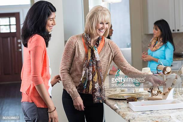 Mujer madura admira joyas en su fiesta de ventas